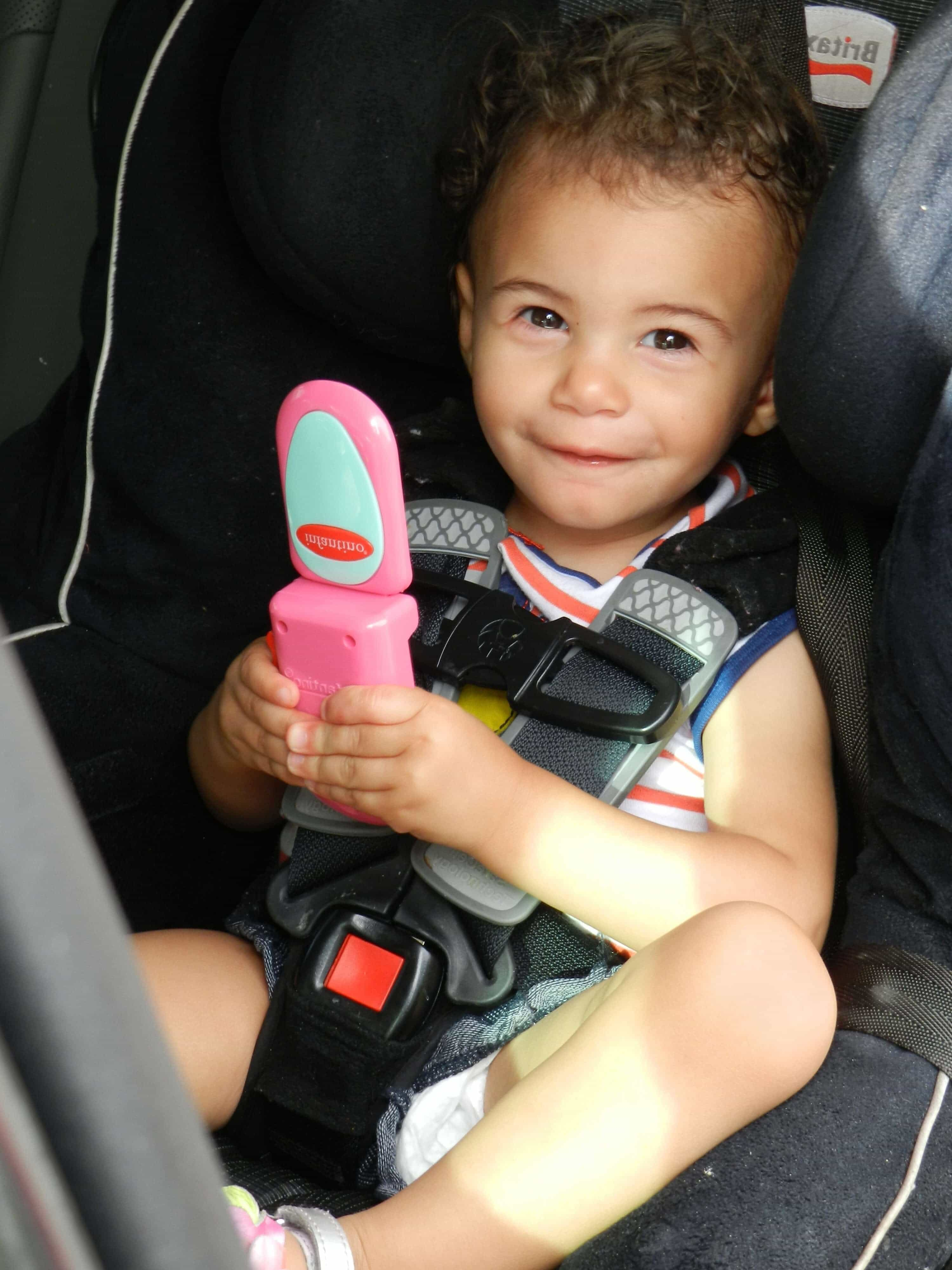 baby in car seat holding a phone